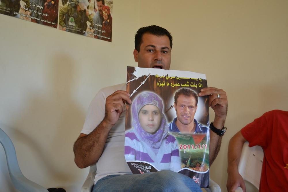 Abdallah Abu Rahma shows victim photos